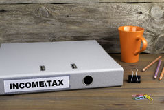 Income and Tax - folder on wooden office desk Stock Photo
