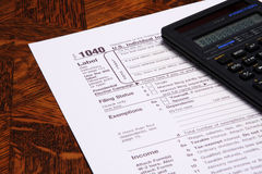 Income Tax Form 1040. And a calculator on a table Royalty Free Stock Image