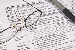 Income Tax Forms. Image of an IRS 1040 form with a pair of glasses and a pen Royalty Free Stock Image