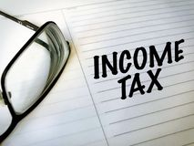 Income Tax. With notebook and glasses Stock Photo