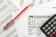 Income tax return with pen and calculator Stock Photo