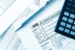 Income tax return with pen and calculator Stock Photos