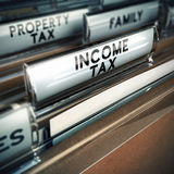 Income Tax - Taxes Concept. Files with close up and focus on the income tax tab, blur effect. Conceptual image suitable for taxes illustration Stock Photo