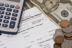 Income Taxes. Preparing a U.S. Tax Form with money in mind royalty free stock photos