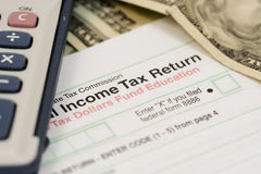 Income Taxes. Preparing a U.S. Tax Form with money in mind stock image