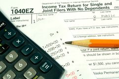Income Taxes. A income tax form with a calculator and pencil Stock Image
