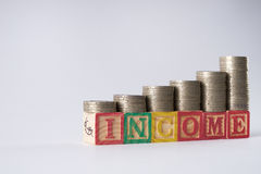 INCOME text written on wooden blocks with stacked silver coins Royalty Free Stock Photography