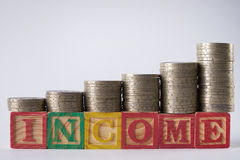 INCOME text written on wooden blocks with stacked silver coins Stock Images