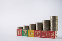 INCOME text written on wooden blocks with stacked silver coins Stock Photography