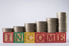 INCOME text written on wooden blocks with stacked silver coins  on white background Stock Photo