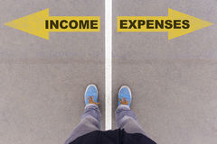 Income vs Expenses text arrows on asphalt ground, feet and shoes Stock Photo