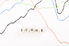 INCOME word written with wooden cubes Stock Photos