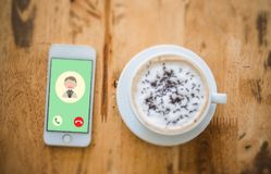 Incoming call from dad in a mobile phone. Top view with a cup of. Coffee on wooden table stock images