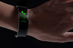 Incoming call icon on smart wristband. A smart wristband is a wearable computing device that closely resembles a wrist watch or other time-keeping device stock photo
