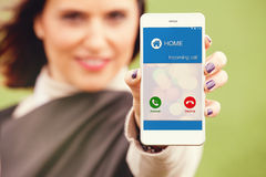 Incoming call on a mobile phone. Woman holding a mobile and showing it to the camera. Incoming call from home on the phone screen stock image