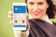 Incoming call from mom in a mobile phone. Woman holding a mobile phone in the hand with incoming call from Mom in the screen royalty free stock photo