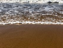 Incoming ocean tide on sand beach royalty free stock photos