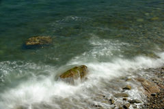 Incoming tidal waves washing over large kelp covered boulders on. A secluded beach Stock Image