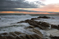 Incoming Tide. Ocean waves and rocks at sunset royalty free stock photography