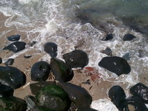 Incoming  tide and  black  boulders Royalty Free Stock Images