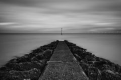 Incoming Tide. Fine Art Monochrome Ethereal Long Exposure, Shooting the tide as it descends upon us moving quite rapidly, With the offshore wind farm on the stock images