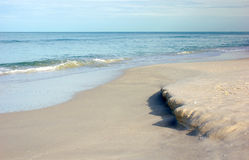 Incoming tide at the gulf of mexico. The incoming tide on bonita beach at the gulf of mexico erodes the sand stock image