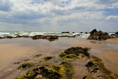 Incoming tide on sand and rocks Royalty Free Stock Photo