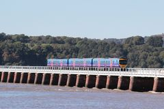 Incoming tide with train on Arnside Viaduct. Cass 185 diesel multiple unit train, unit number 185143, in First TransPennine Express livery crossing Arnside Royalty Free Stock Images