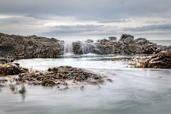 The Incoming Tide. Water flowing over rocks into a rock-pool as the tide changes stock photos