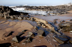 Incoming Wave Forming Pools on Rocky Beach Stock Photography