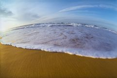 Incoming whitewater on sand, fisheye distortion. Incoming whitewater on sandy beach, spherical distortion royalty free stock images