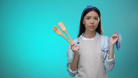 Incompetent housewife in apron holding kitchenware and shrugging shoulders. Stock footage stock video footage