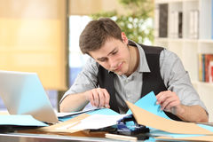 Incompetent messy businessman with disorganized desk. Searching lost documents at office Stock Photo