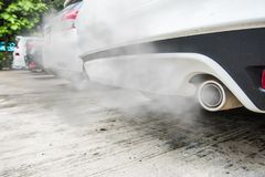 Incomplete combustion creates poisonous carbon monoxide from exhaust pipe of white car, air pollution concept.  royalty free stock image
