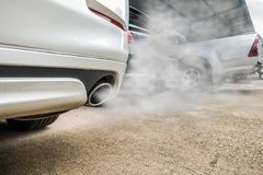 Incomplete combustion creates poisonous carbon monoxide from exhaust pipe of white car, air pollution concept.  stock photos
