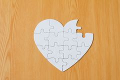 Incomplete heart shape jigsaw puzzle on wooden background.  stock photography