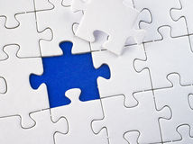 Incomplete jigsaw puzzle. Incomplete white jigsaw puzzle with one piece removed showing blue background royalty free stock photos