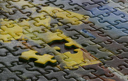 Incomplete Jigsaw Puzzle. Close up of an incomplete jigsaw puzzle with the missing piece on top of the completed part of the puzzle stock photography