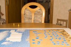 Incomplete Jigsaw Puzzle and Pieces on Table. Detail of Incomplete Jigsaw Puzzle with Blue Sky Pieces Spread Out on Mat - Scenic Puzzle on Dining Room Kitchen stock photography