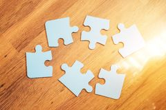 Incomplete jigsaw puzzles on brown background, top view, flat lay. The concept of logical thinking, conundrum. Incomplete jigsaw puzzles on the brown background Stock Image