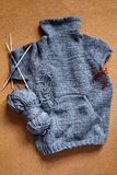 Incomplete knitting gray sweater for child with needles. Hobby for young mother or grandmother royalty free stock photo