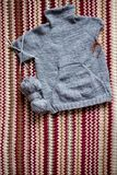 Incomplete knitting gray sweater for child with needles. Hobby for young mother or grandmother royalty free stock image