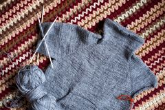 Incomplete knitting gray sweater for child with needles. Hobby for young mother or grandmother stock images