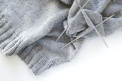 Incomplete knitting project with metal knitting needles close-up on a white background. Knitting a gray wool sweater. The concept royalty free stock photos