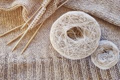 Incomplete knitting project with metal knitting needles close-up. Gray threads, skeins and tangles of Italian wool yarn. The. Concept of knitting, needlework royalty free stock photos