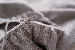 Incomplete knitting project with metal needles close-up. Knitting a gray wool sweater. The concept of hobby, creativity,. Needlework, handmade royalty free stock photography