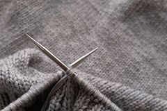 Incomplete knitting project with metal needles close-up. Knitting a gray wool sweater. The concept of hobby, creativity,. Needlework, handmade royalty free stock image