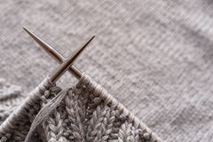 Incomplete knitting project with metal needles close-up. Knitting a gray wool sweater. The concept of hobby, creativity,. Needlework, handmade stock images