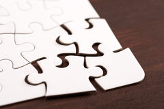 Incomplete puzzle on dark wooden table Royalty Free Stock Photography