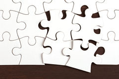 Incomplete puzzle on dark wooden table Stock Images